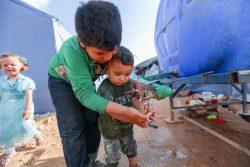 イドリブ北部Maarat Misrin難民キャンプの給水所で手を洗う子どもたち。(シリア、2020年4月23日撮影)