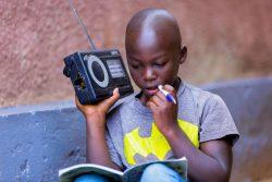 小学校が休校になり、ラジオ番組を通じて自宅で勉強する11歳の男の子。(ルワンダ、2020年4月9日撮影)