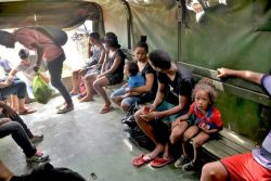 パナマへの入国が許されず、トラックで強制送還されるキューバ人家族とラテンアメリカから来た移民の人たち。(コロンビア)