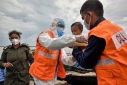 サイクロン「アンファン(Amphan)」の上陸に備え、COVID-19の予防措置をとったスタッフが、危険な地域に住む人たちが安全な場所に避難できるよう手助けする様子。 (バングラデシュ)