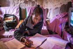 キベラの自宅で勉強するシェイラさん。週に一度、先生から両親の携帯電話に課題が届き、印刷して取り組んだ後、学校に送って先生に添削してもらう。(ケニア、2020年4月7日撮影)