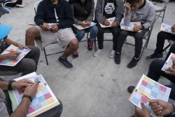 ティファナにある同伴者のいない移民の若者のための施設で、自分たちの中央アメリカからの旅について話す10代の若者たち。(メキシコ、2019年2月撮影)
