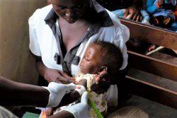 ジュバのプライマリ・ヘルスケア・センターで、上腕計測メジャーを使って栄養不良の検査を受けるファリダちゃん。(南スーダン、2020年4月20日撮影)