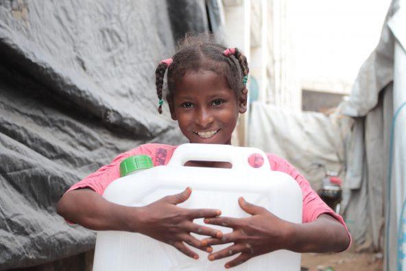 難民キャンプで暮らす女の子。水タンクを抱えている。(イエメン)