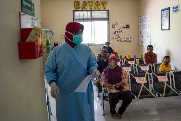 地域の保健センターの室内待合室で待つ患者たち。新型コロナウイルス感染拡大予防のため、座席は身体的距離を測って設置されています。