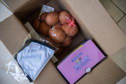 妊婦の女性に配布された栄養セット。マスクや卵、浄水剤などが入っている。