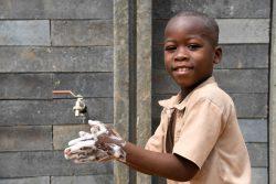 石けんで手を洗う男の子。