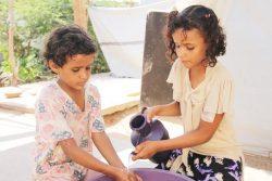 アデンのアル・シャーブ(Al Sha'ab)キャンプで手を洗う10歳のムナさん(右)。(2020年4月27日撮影)