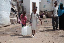 アデンのオマール・ビン・ヤセール(Omar Bin Yasser)キャンプで、給水所で汲んだ水を運ぶ子どもたち。(2020年4月27日撮影)