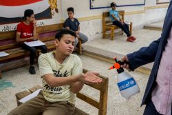 ミニヤー県にある高校で、課題の受け渡しをする間に手を消毒する男の子。(エジプト、2020年5月11日撮影)