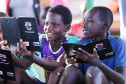 マハマ難民キャンプにある子どもにやさしい空間で、タブレットを用いたユニセフの学習プロジェクトの一環で教育アプリを使って遊ぶブルンジ難民の子どもたち。 (ルワンダ、2019年10月撮影)