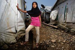 紛争から逃れ、マラウィ(Marawi)郊外にある避難所の仮設住居の横に立つ12歳の女の子。(フィリピン、2019年9月撮影)