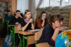 ユニセフとパートナー団体が設立した家族支援センターで、砲撃に備えて窓辺に土のうが積まれた教室で勉強する子どもたち。(ウクライナ、2019年2月撮影)