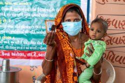 下痢に苦しむ生後11カ月の赤ちゃんの治療のため、亜鉛の錠剤と経口補水塩(ORS)を受け取った母親。(インド、2020年6月17日撮影)
