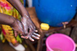 ナイロビ・キベラの給水所で、COVID-19 の感染防止のため正しい手洗いを実践する男の子。(ケニア、2020年4月撮影)