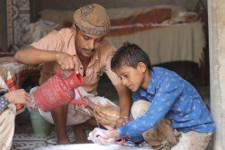 父親から正しい手洗いの方法を教えてもらう10歳の男の子。(イエメン、2020年6月9日撮影)