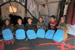 イドリブ県北西部にあるAred al-Jeb難民キャンプの仮設住居で、ユニセフの通学カバンを手にする12歳のウィアムさん(右)と5人の兄妹。(2020年1月撮影)