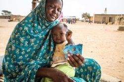 栄養不良に陥った生後6-23カ月の子どもを治療するための微量栄養素パウダーを手にする母親。(モーリタニア、2020年7月9日撮影)