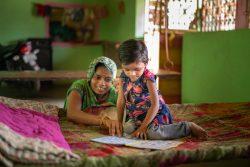 グジャラート州・サンジェリの自宅で、母親と一緒に絵本を見る3歳のドゥビちゃん。(インド、2020年6月27日撮影)
