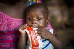 モプティの自宅ですぐに食べられる栄養治療食(RUTF)を口にする、急性栄養不良に苦しむ生後6カ月のアイサタちゃん。(マリ、2019年10月撮影)
