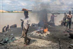 バイエルサ州・イェナゴアで、ゴムなどの廃棄物を燃やして発生した有害な煙の中を歩く男の子。(ナイジェリア、2016年10月撮影) ※本文との直接の関係はありません