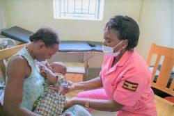 カサンダ保健センターで助産師から正しい母乳の与え方を教わる母親。(ウガンダ、2020年7月1日撮影)