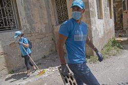 ユニセフとパートナー団体が地元住民と協力し、最も被害が大きかった地域の路上を片付ける様子。(2020年8月8日撮影)