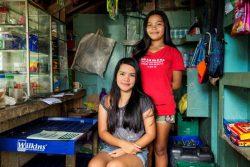 近所で経営しているコンビニエンスストアで店番をする17歳のアレナさん(左)と20歳のアリッサさん(右)姉妹。収入は学費に充てるものだったが、最近は家族の食費に充てられている。(フィリピン、2020年8月10日撮影)