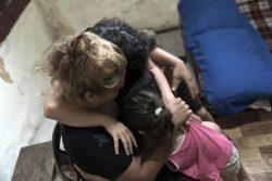 自宅で4歳から11歳の3人の子どもたちを抱きしめるファテンさん。家族はユニセフと現地のパートナー団体から心理社会的支援を受けている。(2020年8月11日撮影)