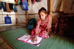 ロヒンギャ難民キャンプの学習センターが閉鎖されているため、母親と先生の助けを借りながら自宅で勉強する9歳のシェフカさん。(2020年6月撮影)