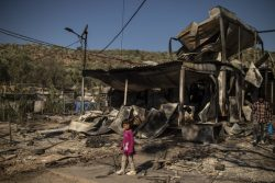 レスボス島のモリア難民キャンプで発生した火災で焼けた建物の前に立つ女の子。(2020年9月9日撮影)