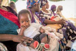 アダマワ州・ヨラの診療所で、母親の膝の上で予防接種を待つ生後4カ月のウィズダムちゃん。(ナイジェリア、2020年1月撮影)