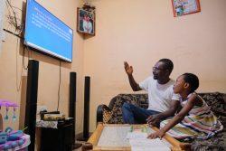 ノートを見ながらテレビ授業を受けるデボラさん(10歳)。理解を助けるため、父親が説明している。(ガーナ、2020年3月撮影)