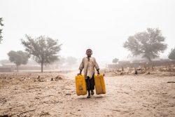 早朝の砂嵐の中、家族のために水汲みをする男の子。(ニジェール、2020年2月撮影)