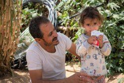 すぐに食べられる栄養治療食(RUTF)を口にする国内避難民の2歳の女の子と、それを見守る父親。(2020年3月撮影)