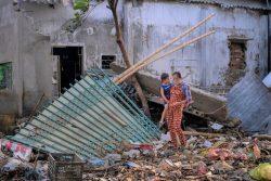 台風の被害を受け、破壊された家の残骸の中を歩く親子。(2020年10月27日撮影)