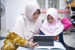 ボゴールの自宅で母親に手伝ってもらいながらオンライン学習をする8歳のジハンさん。(インドネシア、2020年9月26日撮影)