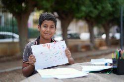 爆発から約3カ月後に行われた子どもの心理社会的支援を目的とした活動で、カラフルな色を使った絵を見せてくれる12歳のフセイン君。(2020年10月28日撮影)
