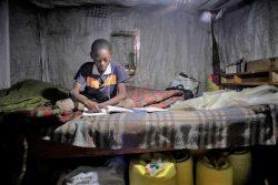 自宅で小学6年生の教科書を読み、練習問題に取り組む11歳のラファエルくん。家族が携帯電話を持っていないため、オンライン学習に参加できずにいる。(ケニア、2020年7月撮影)