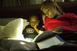COVID-19によるロックダウンの中、男の子(5歳)のために絵本を読む母親(ジンバブエ、2020年4月撮影)