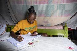 先生が送ってくれたノートを見ながら自宅で勉強する15歳のジルーシャさん。(ケニア、2020年7月撮影)