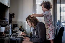 リヨンの自宅でテレワークをする母親のそばで遊ぶ3歳のヴィオレットちゃん。(フランス、2020年3月撮影)