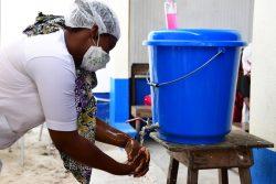 アビジャン郊外にある保健センターで、COVID-19から身を守るためにマスクと手袋を着用し、定期的に手を洗う看護師。(コートジボワール、2020年4月撮影)