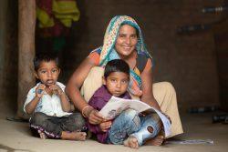 グジャラート州で村に戻った移民への取り組みで、ロックダウン中に就学前教育キットを受け取る親子。(インド、2020年6月撮影)