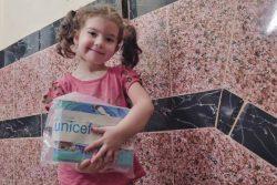 首都カイロで、移民の子どもと家族に配布しているCOVID-19衛生キットや本を受け取った女の子。(エジプト、2020年6月撮影)