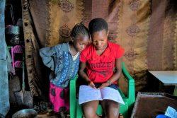 妹に勉強を教える15歳のサラさん。母親が職探しの間、家事や6人の弟と妹のお世話をしている。(ケニア、2020年7月撮影)