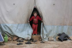 北西部にある避難民キャンプで、テントの中から外を見る子ども。(2021年1月19日撮影)