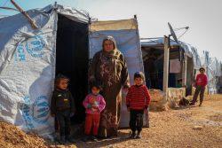 アレッポ県北部の農村部にある避難民キャンプで、テントの前に立つ家族。(2021年1月19日撮影)