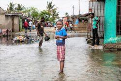 豪雨により水かさが増した村の中に立つ子ども。(2021年1月22日撮影)