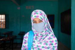 マスクを着用し、教室の前に立つ小学6年生の女の子。COVID-19の影響で数カ月の間、休校していた学校が再開し、テストを受けることができた。(モーリタニア、2020年9月撮影)